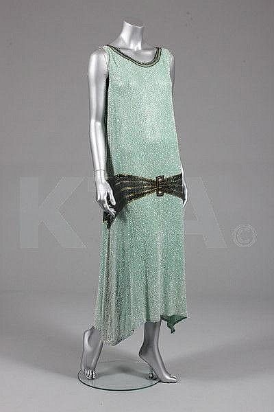 ~A pale green beaded evening gown, circa 1929~ The dress style during the 1920s entailed the elusive hemline to give the illusion of being first long and then shorter with dripping fabrics.