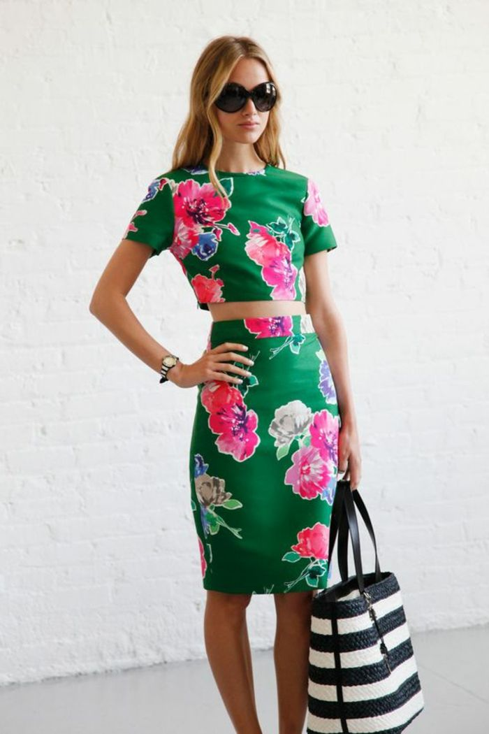 business casual dresses, blonde woman with wavy hair and sunglasses, wearing green and pink floral two piece outfit, knee-length skirt and cropped top, holding big striped bag