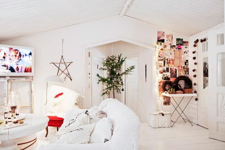 """I vardagsrummet har Katarina gjort en bildvägg med foton på familj och vänner. Soffa """"Tomelilla"""", Ikea. Vardagsrumsbord, köpt begagnat. Tv-skåp av gamla fönster, gjort av Katarinas son Philip. Röd fåtölj """"Emma"""", arvegods. Golvlampa, Kosta. Lampan, fyndad på loppis. På väggen hemmagjord stjärna av pinnar. Kransar, Panduro. Pardörrarna som Katarina fyndat på nätet, leder ner till kontoret och pysselrummet. Runt dörrarna hänger en kottgirlang som är gjord av kottar."""