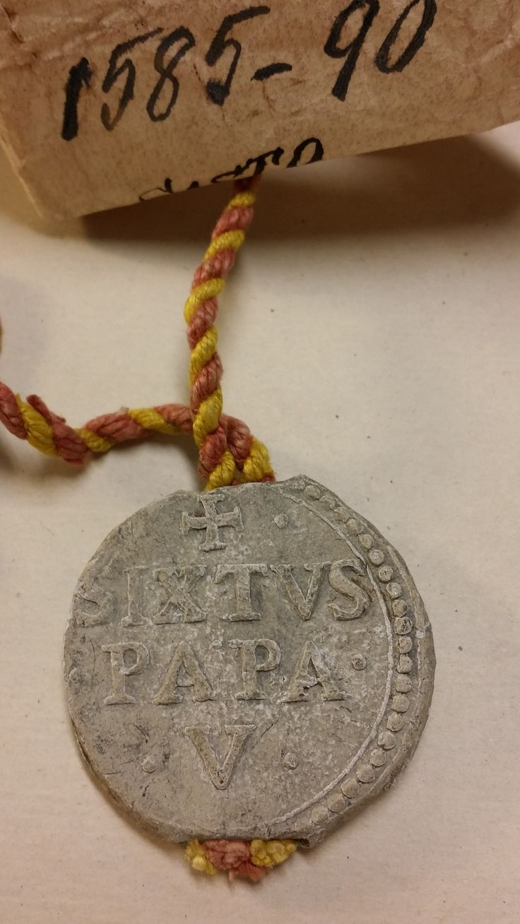 The front of a lead bulla or seal from the Diocesan Archives collection. A bulla was used to authenticate documents issued by both popes and royalty. This particular bulla is attributed to Pope Sixtus V (1585-1590). #tbt #archives #albany #catholichistory