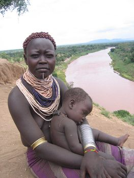 Karo woman and child - Between 1000 and 1500 Karo (Kara) people live on the east banks of the Omo River in south Ethiopia. To enhance the beauty of the Karo bride her abdomen is tattooed with different symbols. The Karo man can have as many wives as he can afford. Usually he has two or three wives.