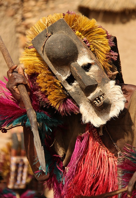 Dancer with a monkey mask and spear symbolizing a hunter