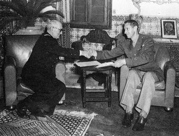 Admiral Jean Darlan (left), commander of the Vichy French armed forces, shares a cup of coffee in Algiers on November 22, 1942, with Lieutenant General Mark W. Clark after the formal signing of a contraversial armistice between Allied and Vichy forces in North Africa. A photograph of Marshal Petain looks over Clark's shoulder.