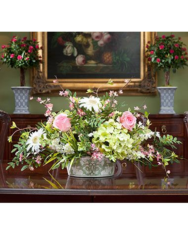 While light and airy, this delicate looking centerpiece is bursting with some very beautiful pastel colored stems. Roses, hydrangeas, gerbera daisies and cherry blossoms are tastefully arranged in our oval crackled green and white porcelain bowl.
