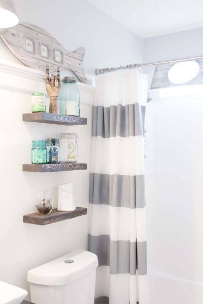 Grey nautical striped shower curtain. Rustic floating shelves above toilet.  Repaint/ stain vanity cupboard.