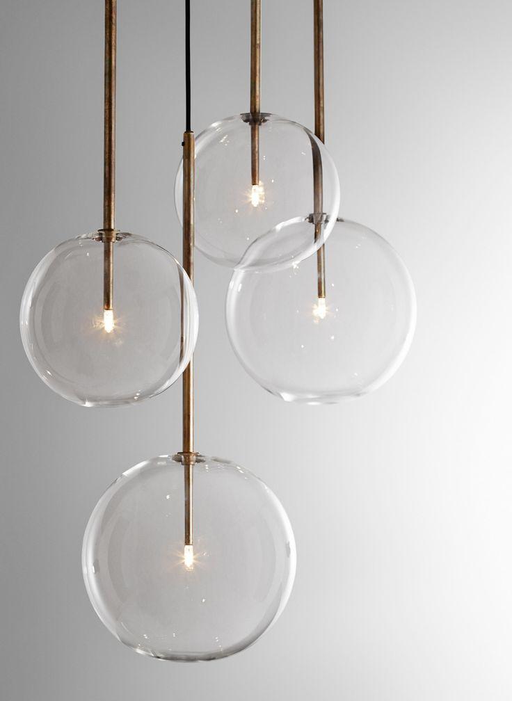 Hanging lamp with halogen point light (20 Watt). Transparent blown glass sphere. Metal parts in hand burnished brass. The hand burnished brass finish..