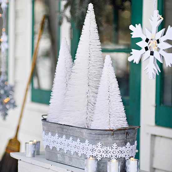 Tiny Frosted Trees Bottlebrush firs look like miniature frosted evergreens when arranged in a wintry bucket or planter. Votive candles add a calming, flickering glow to this outdoor Christmas decoration.
