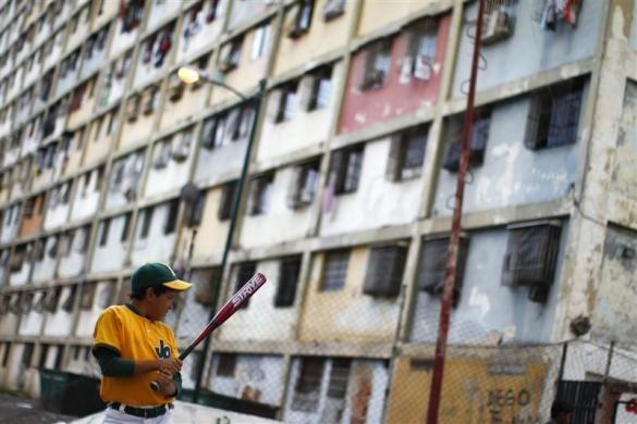 "A boy bats during an informal baseball game at the ""23 de Enero"" neighborhood in Caracas March 2, 2011.  REUTERS/Jorge Silva"