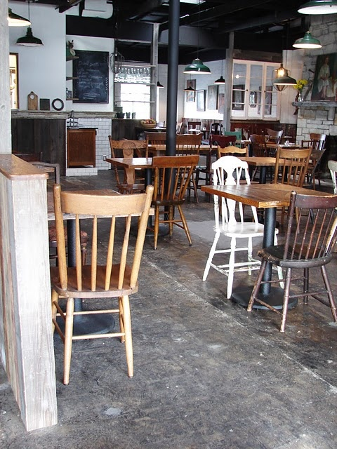 Mismatched, reclaimed wood tables and mismatched chairs.