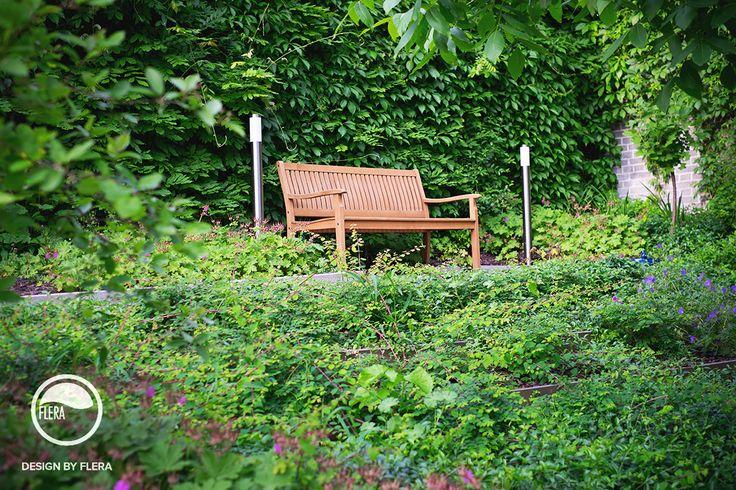 Krásna záhrada s drevenou lavičkou a bohatou zeleňou