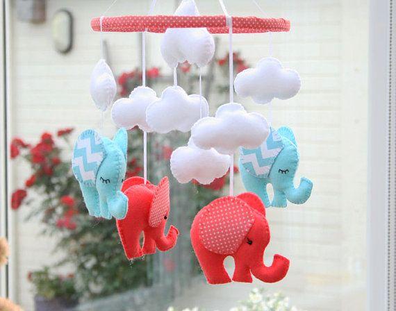 Bienvenido a FlossyTots   Este hermoso móvil de elefante es hecho a pedido   Los elefantes vienen en Coral/hielo azul con orejas de chevron/polka dot y un aro decorado de tela de lunares. En el centro están tres nubes blancas mullidas y una nube encima de cada elefante.  PERSONALIZAR TODO También puede elegir sus propios colores de fieltro y telas para viveros o ropa de cama, convo a mí para discutir!    DIMENSIONES APROXIMADAS: Madera aro 10 Elefantes de 4.5 x 4,5 Gran nube 5 x 3 L...