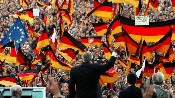 Kanzler der Einheit: Bundeskanzler Helmut Kohl winkt am 20. Februar 1990 bei einer Wahlkampfveranstaltung in Erfurt vor einem Meer von Deutschlandfahnen der Menge zu.