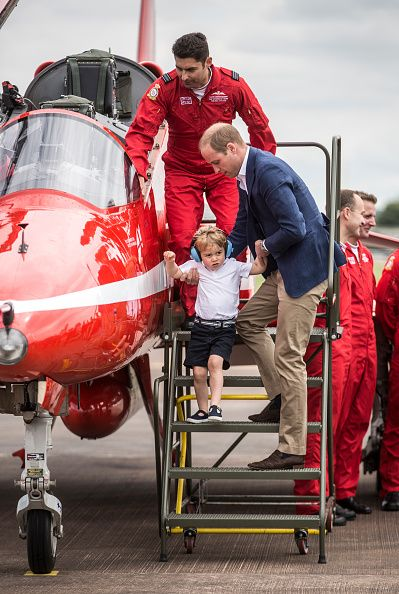 Prince George steps down from the cockpit of a red arrows aircraft as his father Prince William Duke of Cambridge looks on during a visit to the...