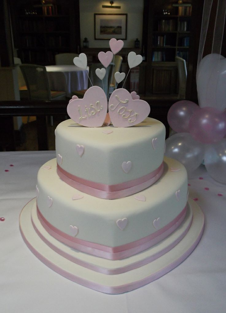 A pale pink themed heart wedding cake in shape and in it's decoration.  Topped with sugar hearts too.