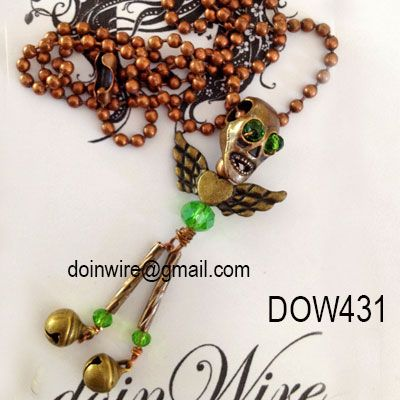 doinWire Pendant - Antique brass tone skull with green crystal eyes, antique brass tone heart/wings body, green crystals, brass tone bell feet on copper tone ball chain.