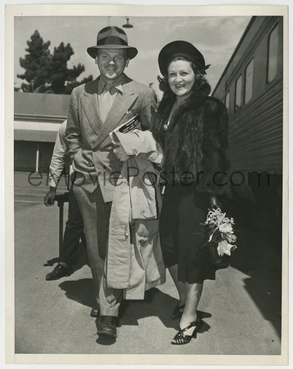 James Cagney and his wife returning home by train. James Cagney was a famous actor from the 1930s to the 1980s. He was a huge success in crime movies in the early 1930s (almost always playing a gangster), and that unfortunately typecast him in those roles, but he continually fought against it, and he made several wonderful non-gangster movies as well. Some of his movie roles include: The Public Enemy, Yankee Doodle Dandy (winner of the Best Actor Academy Award for this film), White Heat…