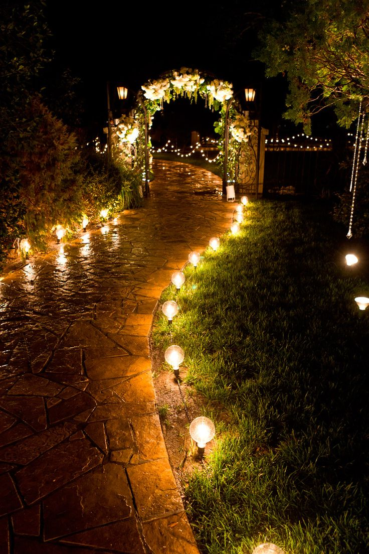 wedding lighting ideas reception. cafe bulbs light the path to a decorated arch at this outdoor evening wedding reception lighting ideas