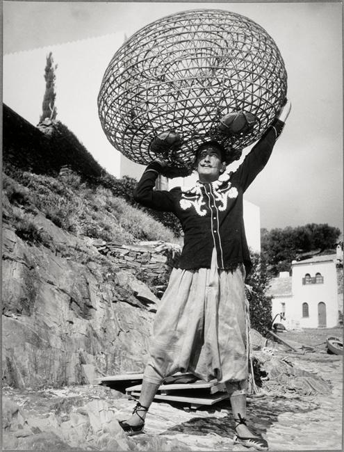 Brassaï ~Dali portant sur sa tête une nasse de pêcheur comme Hercule le globe,1955