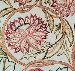Detail of art needlework (https://en.wikipedia.org/wiki/Art_needlework) embroidery in silk on linen, designed by William Morris c. 1878. Seed stitches (small, detached running stitches) are used on the center ribs of these flower petals.