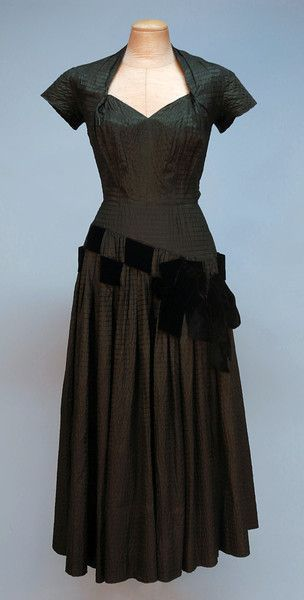 PIERRE BALMAIN PUCKERED SILK COCKTAIL DRESS, 1950's. Forest green taffeta puckered with a horizontal stripe, having cap sleeve and diamond shaped neckline with pleated bust, set-in waist, full skirt with yoke curving toward left hip above two woven black velvet ribbons with bows, back zipper, unlined.