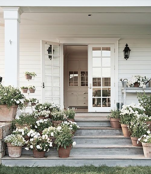 Why this works: all white flowers, all clay pots, wide gray stairs and beautiful white clapboard house.
