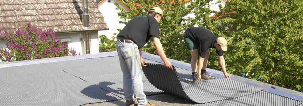 Foto: Zwei Männer beim Aufbau einer Dachbegrünung