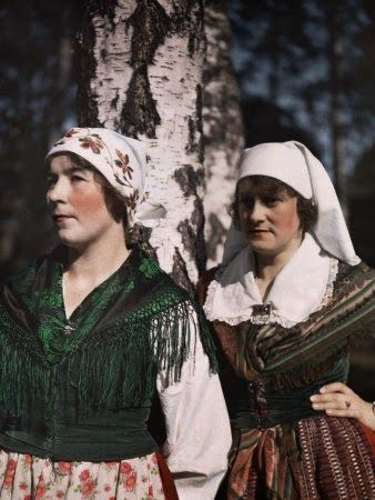 Two women lean against a birch tree   in Central Sweden's forest