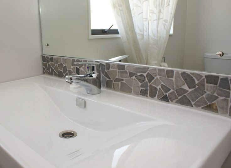 Riverstone Flat Grey Pebble Sheets from Tile Trends. Colours available: natural, black, white, brown and ice. Materials: Natural stone flat pebbles. Dimensions: Interlocking 10x100cm strips and 30cmx30cm sheets. Frost proof. (www.tiletrends.co.nz) Stones like this are a great way to introduce a rustic twist into a space, while still allowing it to appear fresh, modern and stylish. This flat pebble sheet is perfect for an accent wall in the kitchen.