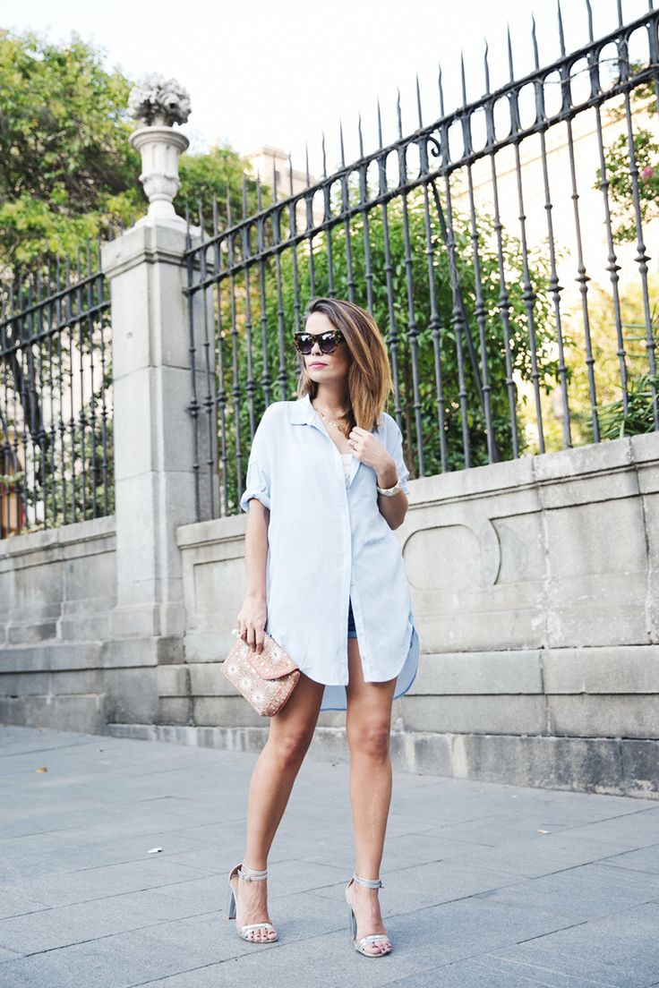Sara Escudero is wearing an oversized pale blue shirt from Bershka, short from Levi's, shoes from ASOS and the purse is from Antik Batik