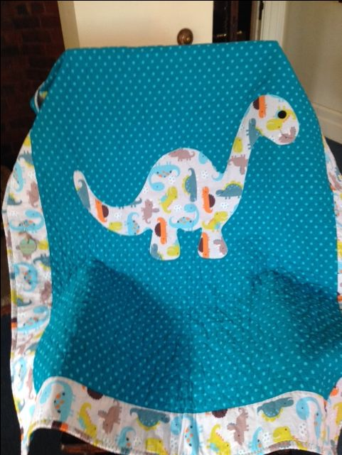 Dinosaurs are not extinct on this large crib quilt/play mat.