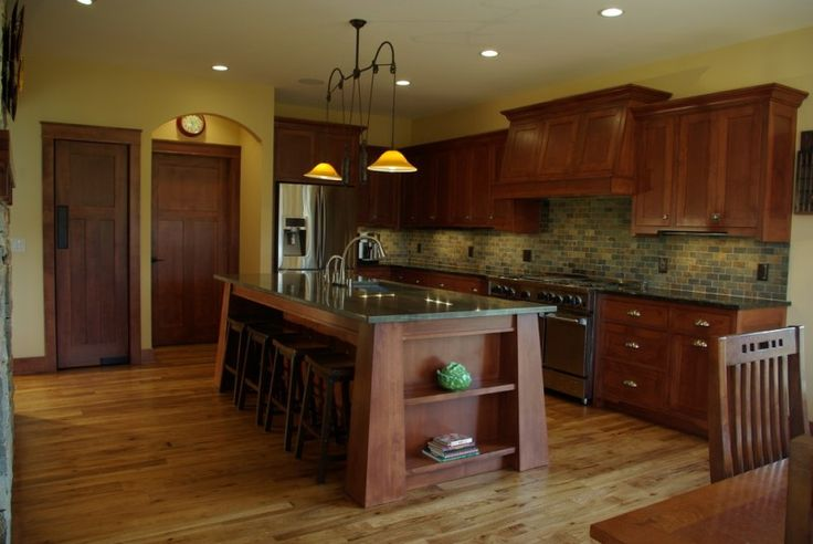 Mission Style kitchen with slanted island posts stools dark green countertop dark wood cabinets dark wood island with open shelves medium toned wood floors of Mission Style Decorating, A Way to Capture Beauty and Warmth to Your Home