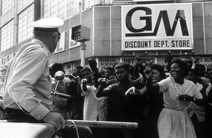 African American protesters taunt a white police officer during a civil rights demonstration.  Birmingham, Alabama, 1963.