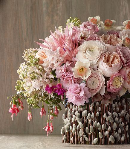 Spring arrangement of White ranuculas, pale pink roses and garden roses, pink spider mums, daffodills, in a pussy willow covered container