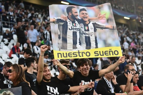 Supporters of Juventus cheer before the UEFA Champions League quarter final first leg football match Juventus vs Barcelona, on April 11, 2017 at the Juventus stadium in Turin.  / AFP PHOTO / Miguel MEDINA