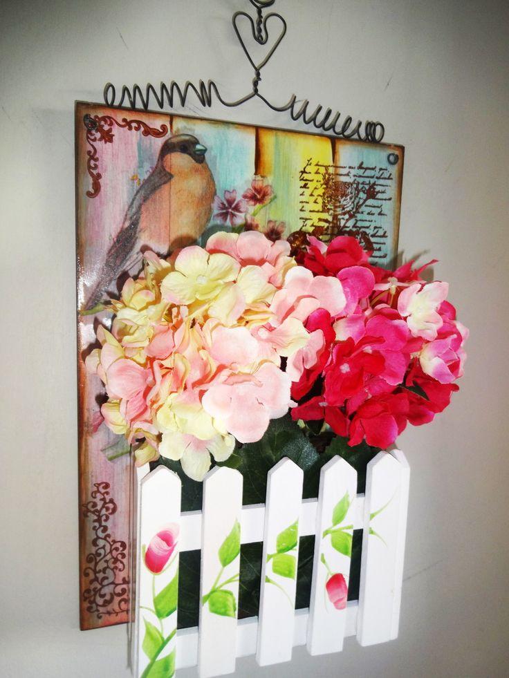 Vaso aéreo em MDF, cerquinha de madeira com flores artificiais de boa qualidade com aparência de flores naturais. Técnicas utilizadas: decoupagem, colagem de cerca de madeira, pintura artística: aplicação de stencil e carimbo. <br>A peça conta com a aplicação de verniz especial para proteção da peça. <br> <br>Esta peça foi elaborada para ser pendurada da parede e as flores ACOMPANHAM a peça, podendo ser trocadas pelo comprador (a troca das flores são de responsabilidade do comprador). <br…