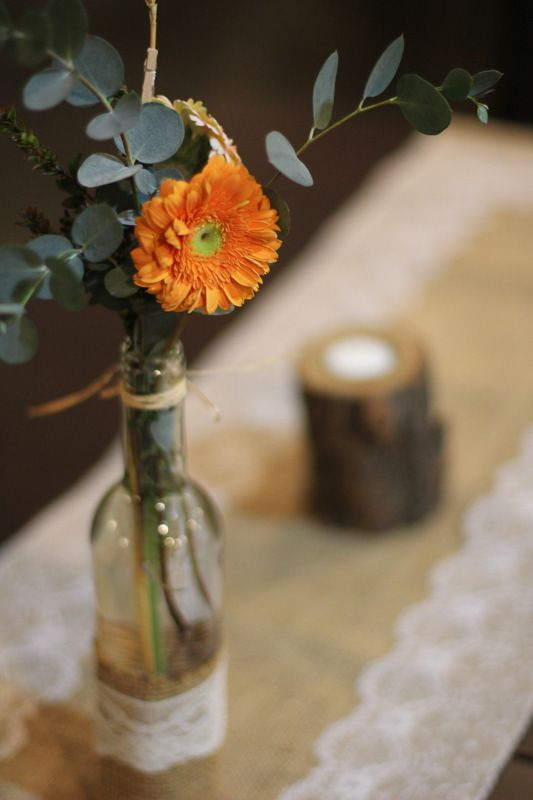 Rustic, hand-made decorations: Burlap table runner, lace-decorated bottles, and wood candle holders