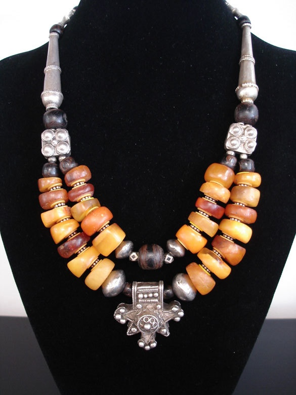 by Luda Hunter   Two strand genuine antique Moroccan natural amber and black coral. Between each amber bead, African vulcanite heishi beads and silver daisy spacers used to protect and cushion the treasured amber beads. Lots of old silver has been used in this necklace with the centre pendant being an old Berber traditional silver cross, 2 antique 2-hole silver spacer beads from Central Asia, Ethiopian coin silver rondelle & end cone beads and old cornerless Tuareg silver beads   1285 AU$