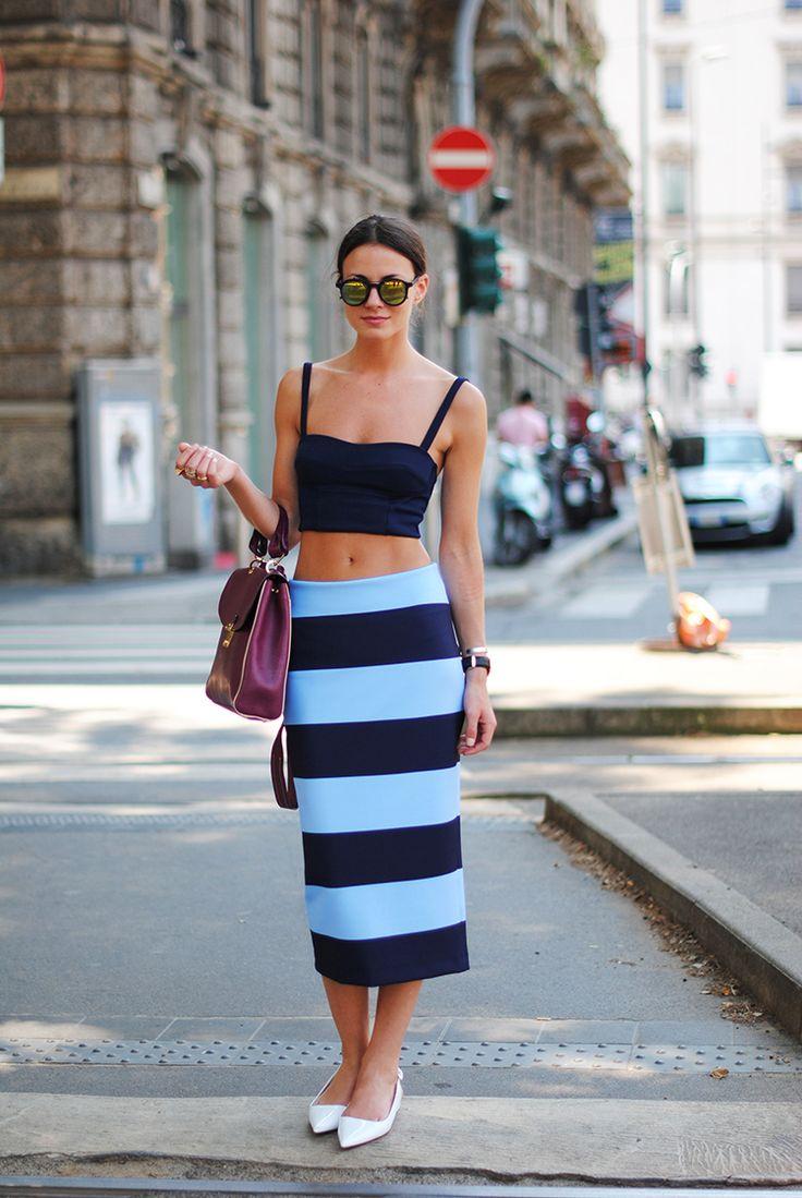 Inspiração street style look com saia lápis mídi listras azul, top cropped azul, sapatilha de bico fino branca, bolsa a tiracolo uva e óculos espelhados.