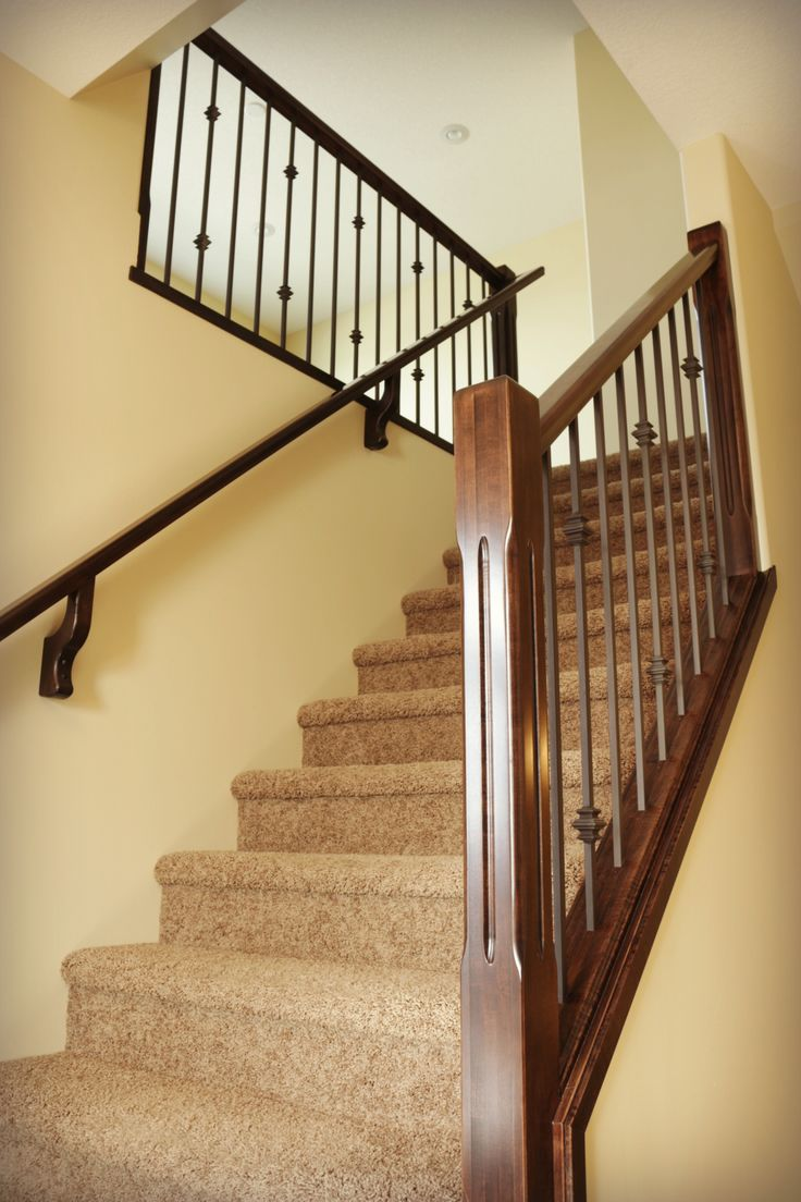 Carpet staircase, iron railing and neutral colours.