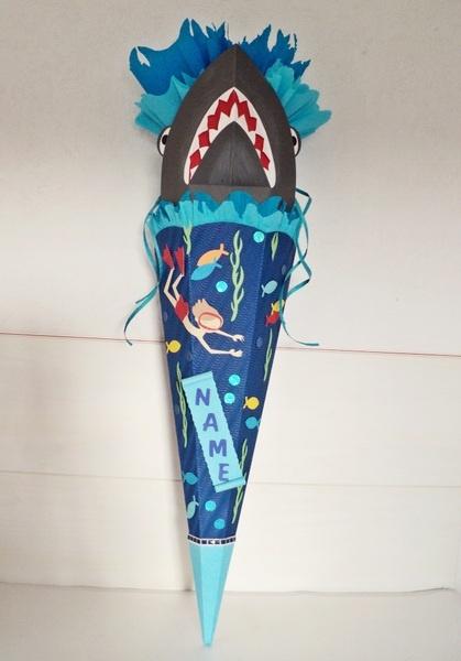 Hier biete ich ihnen eine coole Schultüte mit einem Hai, der gerade aus den Wellen auftaucht, an. Unten im Meer gibt es ein Namensschild,...