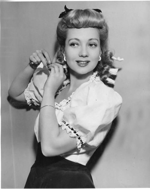 Betty Grable styling her hair with rag rollers