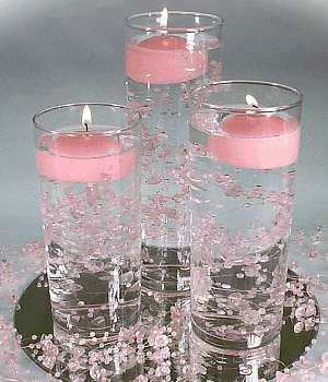 Simple floating candle, water candle, centerpiece adds elegance to an evening wedding. They are inexpensive and easy as a DIY project. Vases available from the dollar store or local craft shop. Use your favorite flowers in the water, babies breath, or water pearls. Match the floating candles to the colors of your event. Our floating candles are available in many sizes, square and round, in many wonderful colors. For a real punch of color try our floating gel candles…