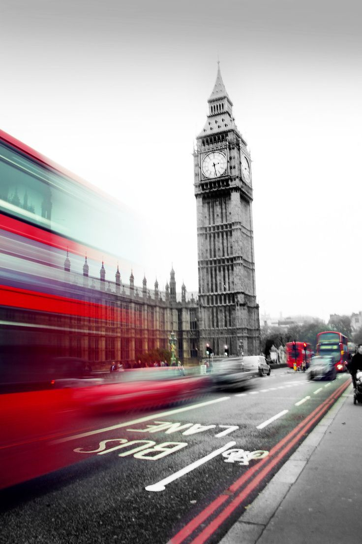 Elizabeth Tower, also known as Big Ben, in London with a red double decker bus zooming by.