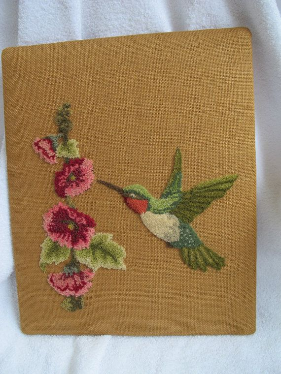 Beautiful vintage 1970s shabby chic wall hanging with elegant punch needle embroidery on a gold burlap background. Lovely hummingbird in shades of green and pink feeding on cheerful hollyhocks. Nice large format at 16 by 13 inches in size. Finished on back with hanging wire. Front is