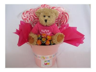 Happy Birthday Teddy. Comes with an arrangement of delicious lolly pops in strawberry flavour and is presented in tin with Happy Birthday ribbons.