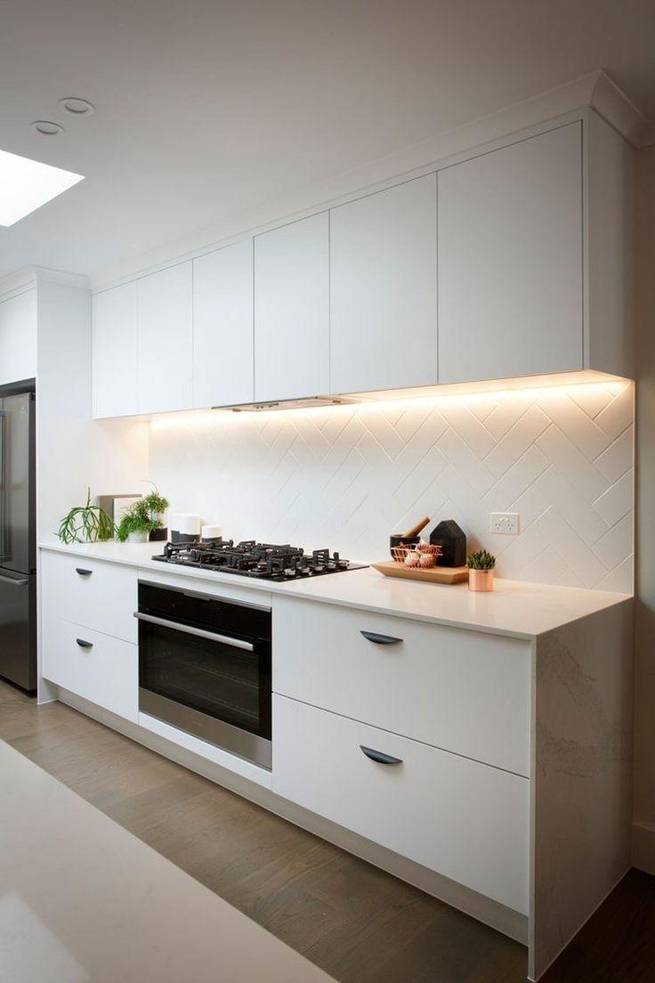 Kitchen all-white quartz countertop and tiled backsplash