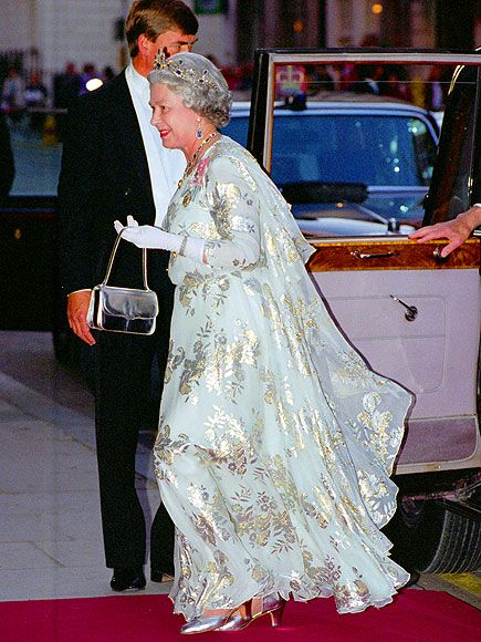 On a return trip to the sovereign Arab state in 1995, Queen Elizabeth glowed in a flowing silver gown embossed with floral details, plus metallic accessories and glamorous gems.
