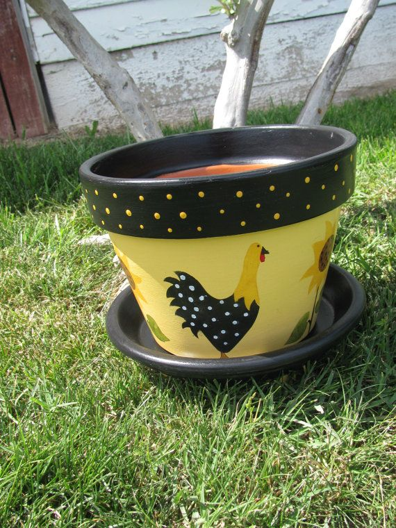 This is an 8 inch terracotta Flower Pot. Pot is painted in yellows and balck with sunflowers and chickens all the way around the pot. Saucer is included