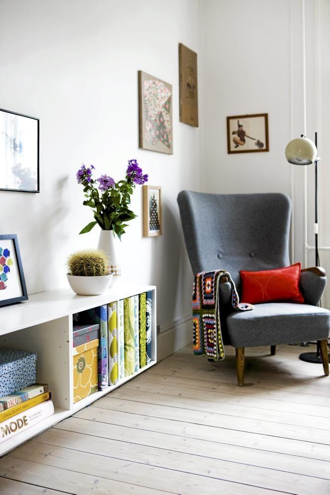 Dette hjørnet inviterer til en tidsreise. Både bord, lenestol, hekleteppet og lampen bærer klare referanser til 60- og 70-tallet. Permene og eskene i hyllen er i ulike farger og mønster, men i samme retro-inspirerte stil.