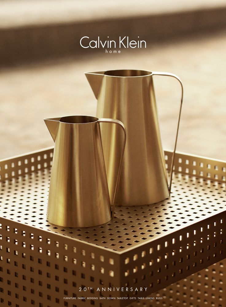 The iconic burnished gold pitcher  sits atop a solid bronze perforated metal side table from Calvin Klein Home.